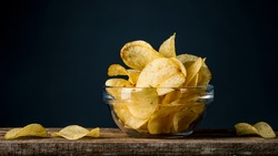 Potatoes Chips. Chips in glass bowl good for snack for beer or ale on natural wooden table. Good for beer festival, pub, restaurant advertising. Food and Drink photography. Macro high resolution Photo