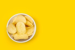 Potatoes chips in a ceramic bowl on a yellow background in a top view