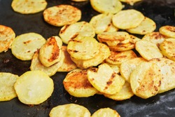 Potatoes cut to round chips grilled on electric grill, closeup detail on slices with brown burn marks