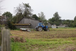 Potatoes field with old wheeled tractor with potato harvesting attachments, potatoes harvesting on an autumn day on old wooden barn background, Russian countryside farming rural landscape