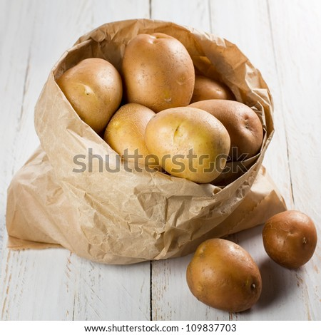Potatoes in paper bag on vintage wooden table