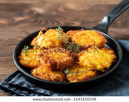 Potatoes pancakes latkes, flapjacks, hash brown or potato vada on brown wooden table. Copy space for text. Stock photo ©