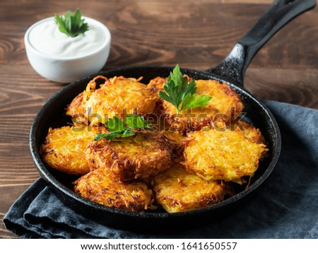 Potatoes pancakes latkes, flapjacks, hash brown or potato vada with white greek yoghurt or sour cream on brown wooden table. Copy space for text. Stock photo ©