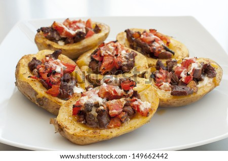 Potatoes stuffed with meat, vegetables and sour cream