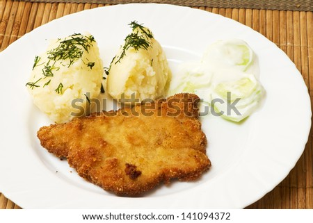 potatoes with dill, pork chop and salad with cucumbers and cream - stock photo