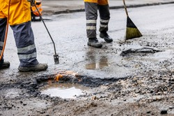 pothole repair - maintenance service workers working on the road
