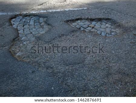 Potholes in asphalt road show a previous stone pavement layer.  #1462876691