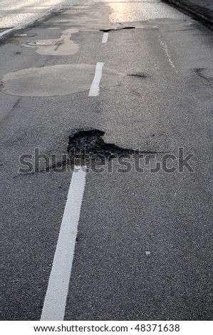 Potholes on a road with white dividing lines