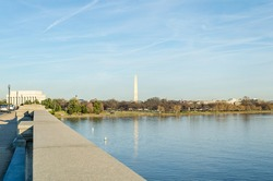 Potomac River Calm Waters and Washington Monument Obelisk in Background. Arlington Bridge Leads to Lincoln Memorial.  Washington DC, USA. Sunny Day with Blue Sky