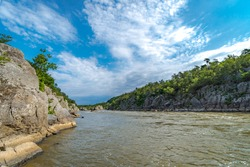 Potomac River running through mountains with tree's hanging over the edge on a clear blue sky sunny day.