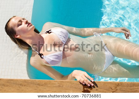 Potrait of a sensual young girl resting in swimming pool - Outdoor