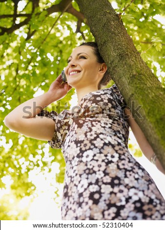 potrait of mid adult italian woman leaning on tree at sunset and talking on mobile phone. Low angle view, vertical shape.