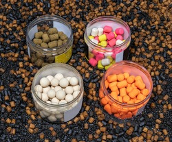 pots of carp fishing hook baits including pop ups and wafters on a bed of pellets