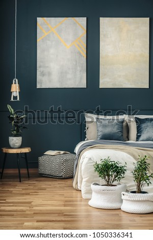 Potted plants in yarn baskets in front of a cozy bed in a dark, navy blue bedroom interior with modern art and wooden panels