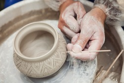 potter make a decorative pattern on pot