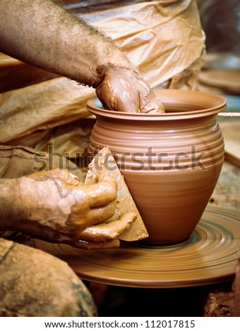Potter making clay pot on the pottery wheel. Artisan hands and pottery tools, close-up.