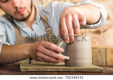 potter, stoneware, ceramics art concept - craftsman's hands connect the cup and the handle made of raw clay, master fingers work with pieces of clay, male sits at a workshop behind the table