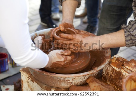 Potter teaches cooking pots his assistant. Close-up