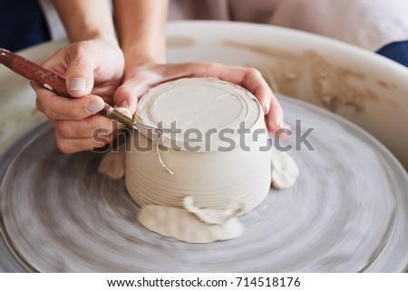 potter using trim tool to get...