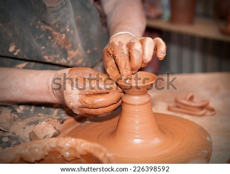 potter working on the lathe with a lump of clay