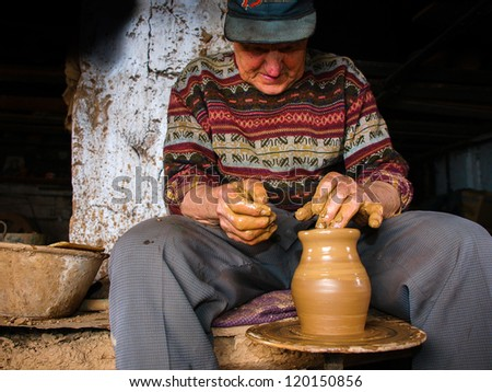 potter working with clay on pottery wheel