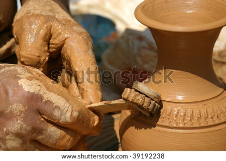 Potters hands creating a traditional clay vase on the turning wheel - stock photo