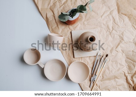 Pottery ceramic products of blank beige color. Fired and polished. Bowls, cups and vase. Top view. Сток-фото ©