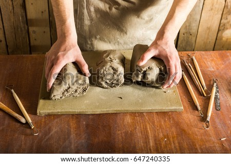pottery, clay, ceramics art concept - closeup on hands of young master with the large pieces of fireclay