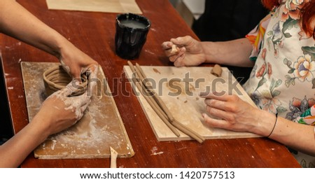 Pottery masterclass process as of two girls seating one on the other by wooden table, their hands in picture making clay mug or bowl