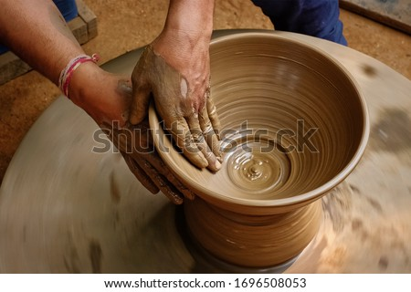 Pottery - skilled wet hands of potter shaping the clay on potter wheel. Pot, vase throwing. Manufacturing traditional handicraft Indian bowl, jar, pot, jug. Shilpagram, Udaipur, Rajasthan, India Сток-фото ©