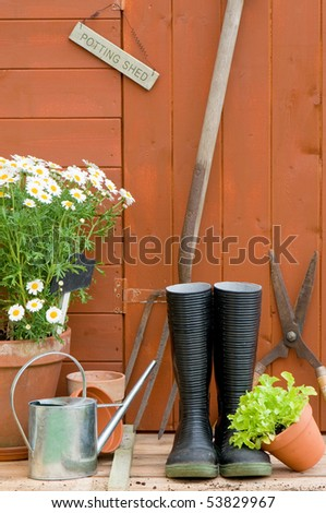 Potting shed with wellington boots, tools, watering can and garden pots