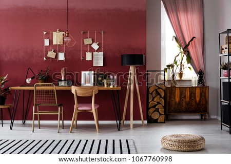 Pouf and striped rug in dark home office interior with wooden chair at table next to lamp
