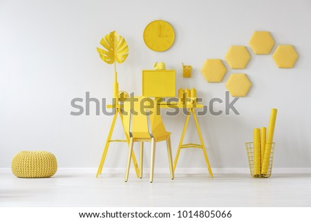 Pouf next to chair at desk with monstera leaf against white wall with honeycombs in yellow room interior #1014805066