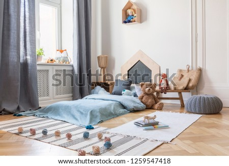 Pouf, rugs and plush toy in bright child's bedroom interior with window and blue bed. Real photo