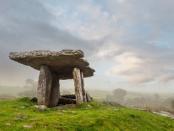 Poulnabrone Dolmen relict building in County Clare near Ballyvaughan town, famous Burren area of Ireland, Beautiful sun rise sky, Green grass in foreground. Fine example of Irish history