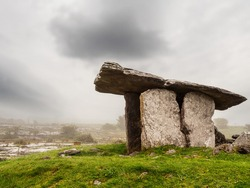 Poulnabrone Dolmen relict building in County Clare near Ballyvaughan town, famous Burren area of Ireland, Beautiful sun rise sky, Background in a haze. Green grass in foreground.  Irish history