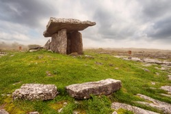 Poulnabrone Dolmen relict building in County Clare near Ballyvaughan town, Ireland, Beautiful cloudy sky and background in a haze. Green grass in foreground. Irish national monument