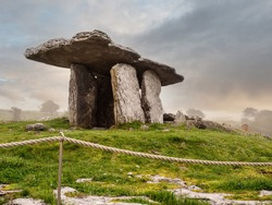 Poulnabrone Dolmen relict building in County Clare near Ballyvaughan town, Ireland, Beautiful sun rise sky, Background in a haze. Fine example of Irish history