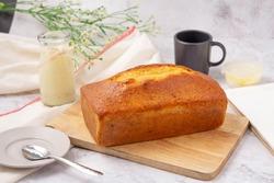 Pound cake with lemon glaze on cutting board, milk in glass bottle.