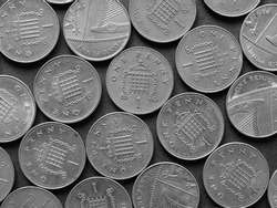 Pound coins money (GBP), currency of United Kingdom, over black background in black and white