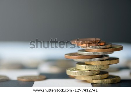 Pound sterling coins stacking on chess table with black background.Currency exchange concept.-Image. #1299412741