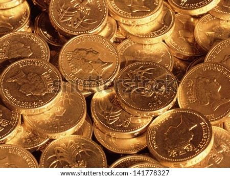Pound sterling coins under tungsten lighting to create gold effect