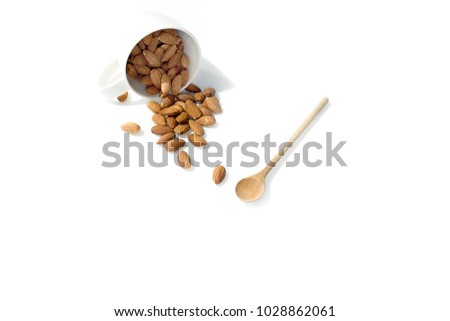 Pour Almonds from white cup and wood spoon, isolated on white background #1028862061