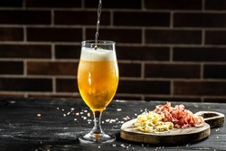 pour beer into a tall glass with a thick foam, dried fish on wooden background. Beer brewery concept. Snack for beer dried smelts. Beer background.