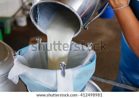 Pour raw milk into a bucket