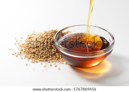 Pour the oil into the sesame oil placed on a white background. Foto stock ©