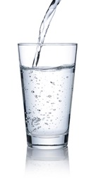 Pour water into a clear glass placed on a white background.