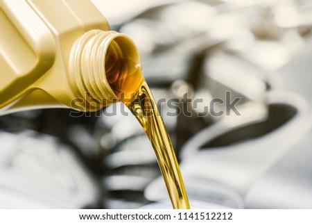 Pour yellow motor oil into car engine. Maintenance service change liquids and fluid.