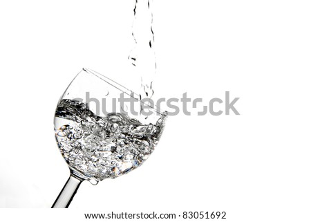 Pouring a clear drink into a wine glass and making bubbles.