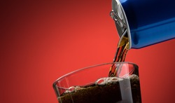 Pouring a refreshing sugary soft drink from a can into a glass